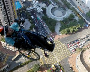 Lai Chi-wai, a paraplegic climber, attempts to climb the 320-metre tall Nina Tower using only his...