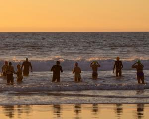 A group of swimmers go for an evening swim in the Pacific Ocean. REUTERS