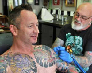 Chris Dick receives a top-up tattoo from Chris Downing, of Crazy Horse Tattoos. PHOTOS: CHRISTINE...