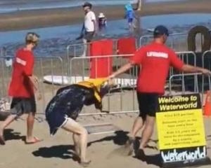 A woman being dragged by male staff member of Auckland water park. Photo: RNZ/Supplied