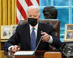 US President Joe Biden signs an executive order repealing former President Trump's ban on...