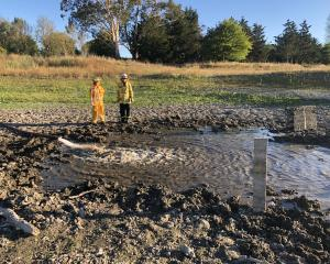 Swannanoa firemen Assina Dalglish, left, and Scott Pilkington pour water into Whites Pit as part...