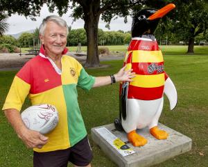 Snow (Ian) Richards beside Snow the penguin, which was designed and named in his honour to...