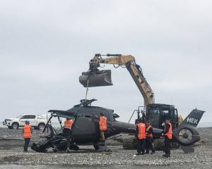 The wreckage of the helicopter is removed from Kēkerengū Beach. Photo: NZ Herald