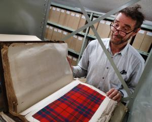 Taking a peek at an old Oamaru Woollen Mill tartan sample book is Waitaki Museum and Archive...