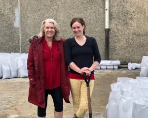 Taieri MP Ingrid Leary (left) and Volunteer South manager Leisa de Klerk help fill sandbags at...