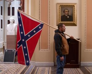 Kevin Seefried, a supporter of US President Donald Trump, holds a Confederate flag outside the...