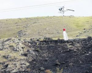 A helicopter is used to help fight a fire above the Lake Waitaki dam village yesterday. PHOTO:...