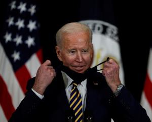 US President Joe Biden removes his mask to speak to staff during a visit to the State Department...