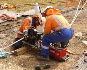 Workers join conductor cable by applying tonnes of clamping pressure on a sleeve to join the two...