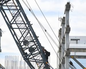 A man (centre) scales a crane in the Invercargill CBD. Photo: Laura Smith