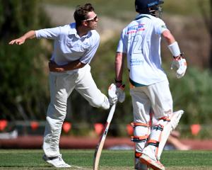 Taieri spinner Ben Lockrose bowls as Green Island batsman Nick Kelly backs up during their...