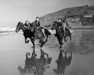 Galloping along the sand in a now-well-known 1958 shot are (from left) Alison Lindsay (nee Dean,...
