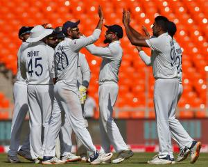 India players celebrate after taking a wicket against England during the first day of the fourth...