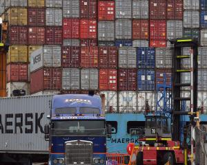 A truck leaves Port Otago on Friday with the container ship Maersk Innoshima behind. PHOTO:...