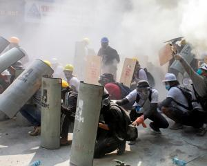 Protesters take cover as they clash with riot police in Yangon on Sunday. Photo: Reuters