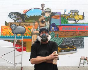 Artist Sean Duffell takes a quick break while apply the finishing touches to his Tower Lane mural...