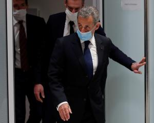 Former French President Nicolas Sarkozy leaves after the verdict in his trial on charges of...