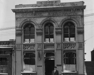 An unidentified person stands in the snow in front of the Sew Hoy building in Dunedin in the late...