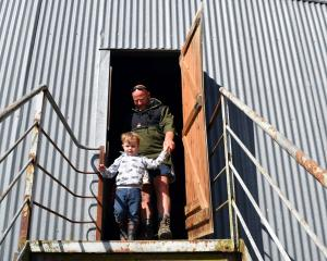 Farmer Cameron Clark, of Owaka, helps his grandson Clay (3) down the back entrance to the auction...
