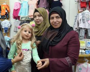 Former Syrian refugee sisters (from left) Malak and Nour Akkam, and their mother, Aicha Dawara,...