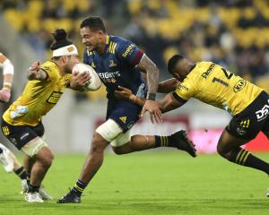 Highlanders loose forward Shannon Frizell attempts to burst through the tackles of Hurricanes...