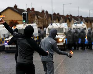 Rioters throw burning bottles at police on the Springfield Rd as protests continued in Belfast on...