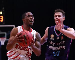 Perth Wildcats guard Bryce Cotton takes the ball to the hoop on New Zealand Breakers forward Tom...