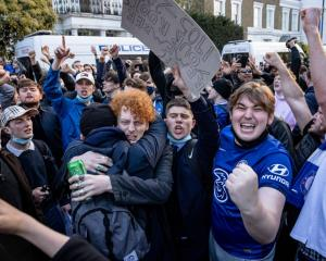 Chelsea fans celebrate the news of the Super League's demise outside the club's headquarters...