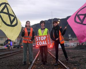 Protesters opposing the use and transport of coal block the railway tracks near the Dunedin...