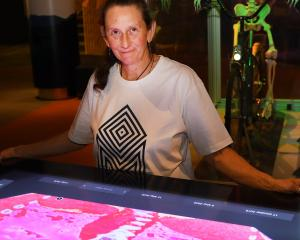 Otago Museum science communicator Catriona Gower with an interactive exhibit showing, in red...
