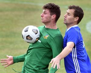 Green Island's Matt Brazier controls the ball on his chest as Mosgiel's Cam McPhaill defends...