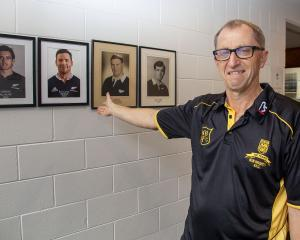 New Brighton Rugby Club centenary committee chairman Wayne Turner with photos of the club's four...