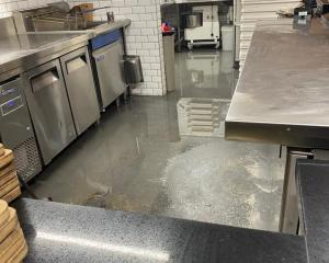 Water inside Fire & Slice's kitchen, a pizzeria in Sumner, after torrential rain flooded the...