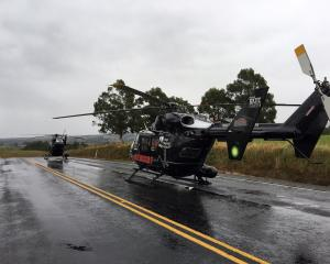 Rescue helicopters on the highway near the crash site. Photo: Richard Davison