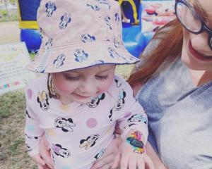 Samantha Flaws, who steadies her daughter Layla at her second birthday, in Townsville, says she...