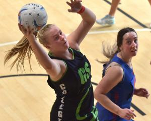 College attacker Ivy McLean grabs the ball watched by Uni Albion A defender Bree Andrews at the...