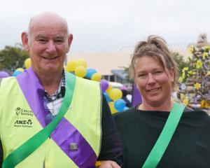 Cancer Society volunteer Henry McHoull and his daughter Angela both don green ribbons,...