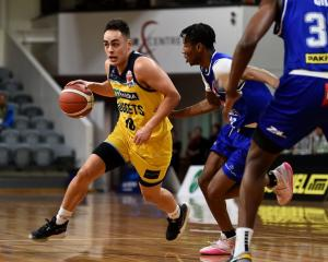 Otago Nuggets guard Richie Rodger drives while Wellington Saints guard Kemar Roach defends him...