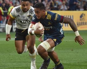 Highlanders blindside flanker Shannon Frizell runs the ball ahead while Hurricanes second five...