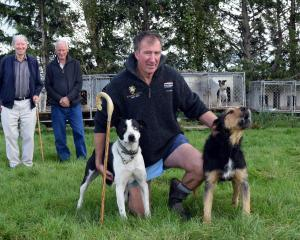 Kauana Sheep Dog Trial Club member Rod Coulter pats his heading dog Blue and huntaway Bruce, as...