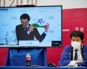 International Olympic Committee (IOC) executive director Christophe Dubi is seen on a screen as...