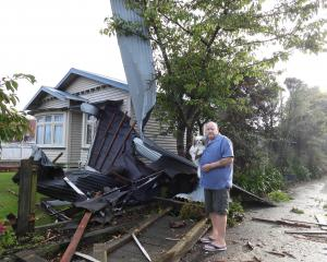 New Marlborough St resident Robert Hill surveys the roof that landed in his front yard overnight,...