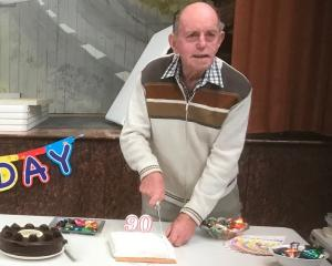 Lester Harvey, of Mosgiel, cuts the cake during a celebration for his 90th birthday thrown by the...