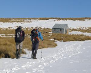 Two trampers make their way towards Wire Yards Hut in the Hawkdun Range, 