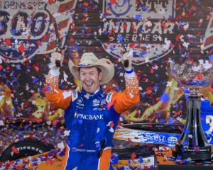 Scott Dixon fires off six shooters as he celebrates his victory in the Genesys 300 race at Texas...