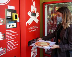 Fabrizia Pugliese collects her order at the first automatic pizza vending machine, which is...