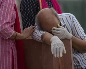 A man grieves on the banks of the Ganges at Garhmukteshwar in the northern state of Uttar Pradesh...
