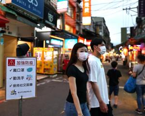 "People walk past a sign reading ""Wear protective face mask, wash your hands and keep social..."