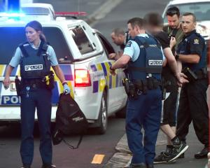 Dunedin police take a man into custody following an alleged theft in North Dunedin yesterday....